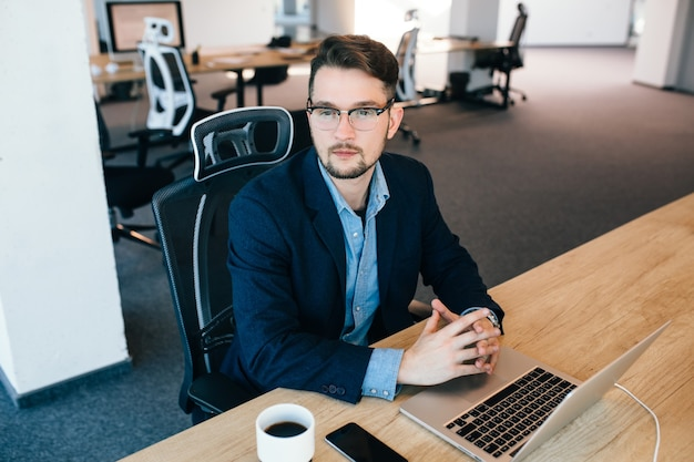 Un homme aux cheveux noirs attrayant est assis à la table du bureau. il porte une chemise bleue avec une veste noire. il regarde sur le côté. vue d'en-haut.