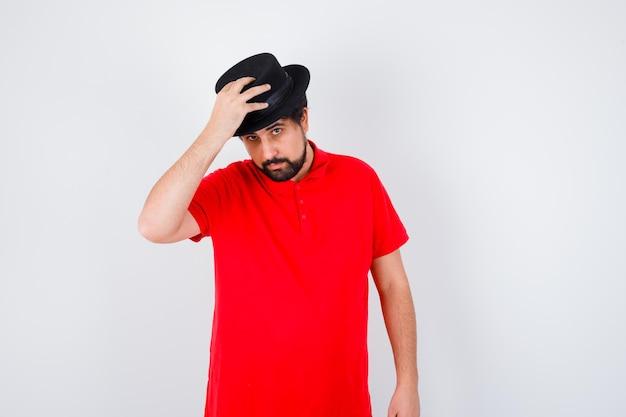 Homme aux cheveux noirs en chapeau de réglage de t-shirt rouge, vue de face.