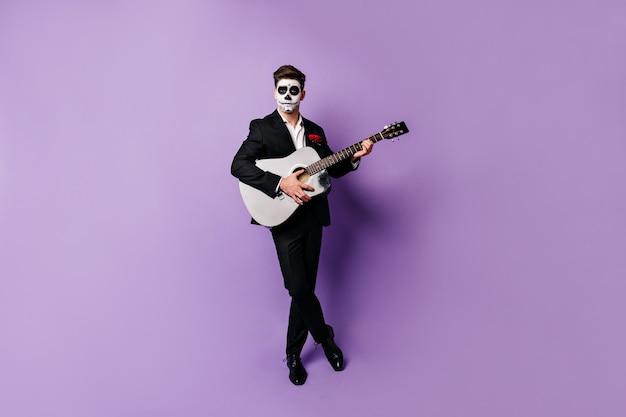 Homme aux cheveux noirs en costume élégant et visage peint en forme de crâne joue de la guitare, regardant dans la caméra avec un regard impassible.