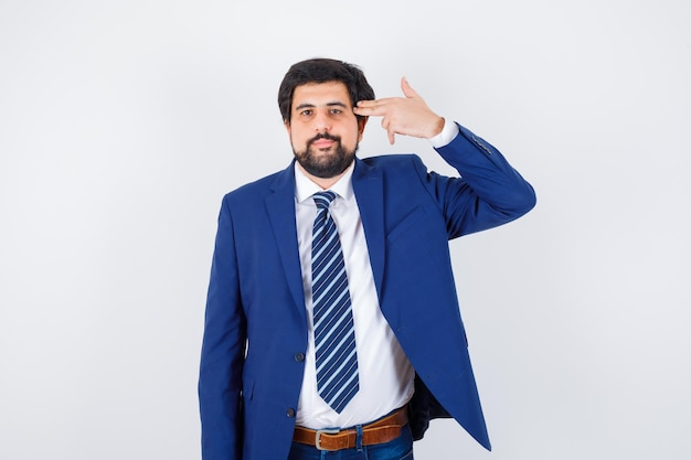 Homme aux cheveux noirs faisant un pistolet vers sa tempe en chemise blanche, veste bleu foncé, cravate et ayant l'air de s'ennuyer. vue de face.