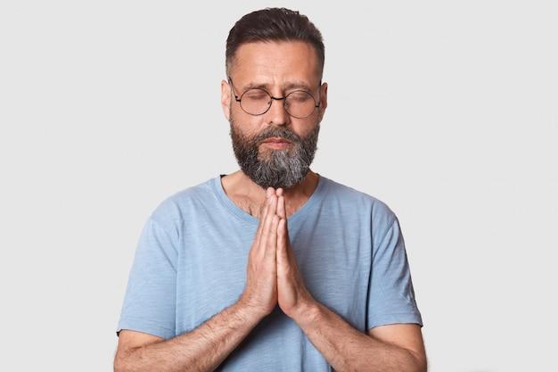 Homme aux cheveux noirs en lunettes rondes, vêtu d'un t-shirt gris décontracté, se tenant la main, priant pour quelque chose
