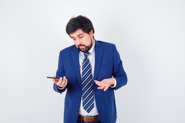 Homme aux cheveux noirs regardant le téléphone tout en parlant en chemise blanche, veste bleu foncé, cravate et l'air confus, vue de face.