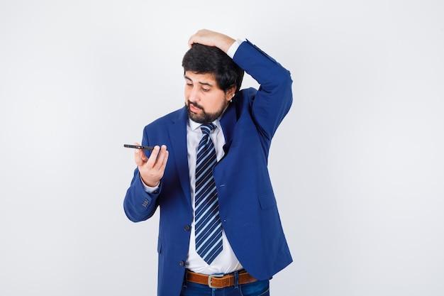 Homme aux cheveux noirs regardant le téléphone tout en parlant en chemise blanche, veste bleu foncé, cravate vue de face.