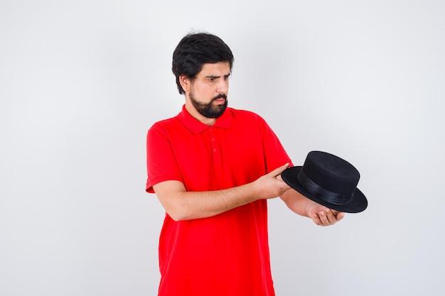 Homme aux cheveux noirs en t-shirt rouge regardant son chapeau, vue de face.