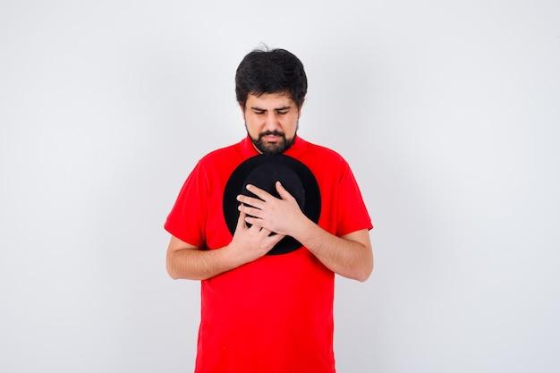Homme aux cheveux noirs en t-shirt rouge serrant sa casquette et ayant l'air plein d'espoir, vue de face.