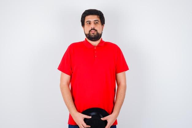 Homme aux cheveux noirs en t-shirt rouge tenant un chapeau et l'air calme, vue de face.