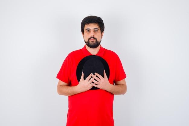Homme aux cheveux noirs en t-shirt rouge tenant un chapeau sur la poitrine et l'air calme, vue de face.