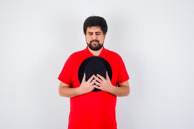 Homme aux cheveux noirs tenant un chapeau sur la poitrine en t-shirt rouge et l'air contrarié. vue de face.