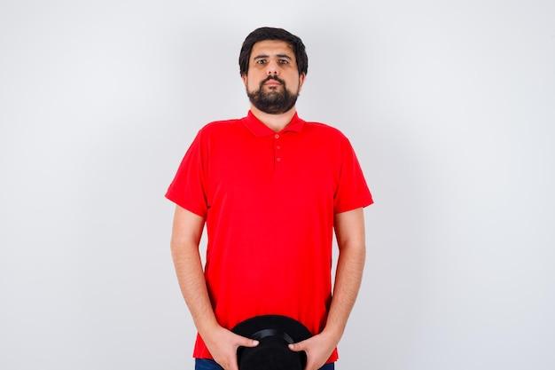 Homme aux cheveux noirs tenant un chapeau tout en regardant loin en vue de face de t-shirt rouge.