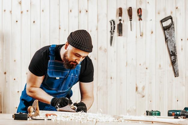 Un homme aux cheveux noirs traitant une barre en bois avec un avion jack noir