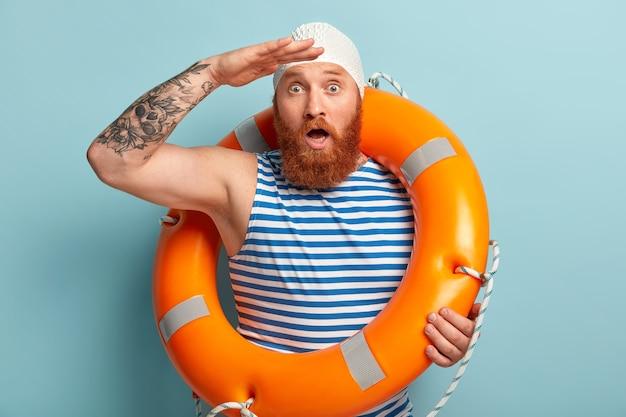 Un homme aux cheveux roux barbu choqué regarde étonnamment loin, garde la paume près du front, la bouche grande ouverte