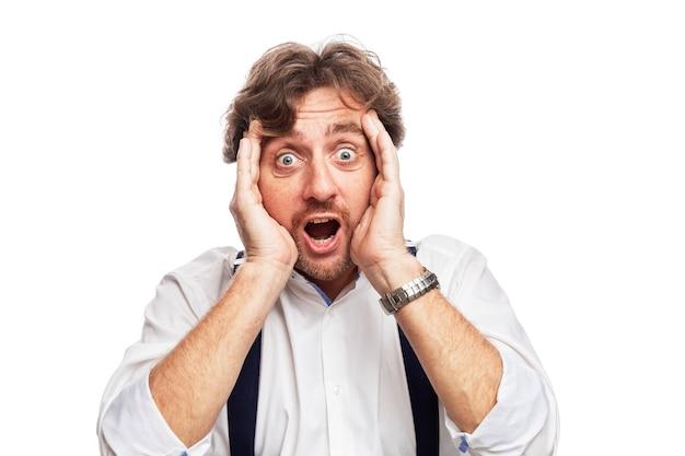 Un homme aux cheveux roux en chemise blanche est choqué. isolé sur un mur blanc.