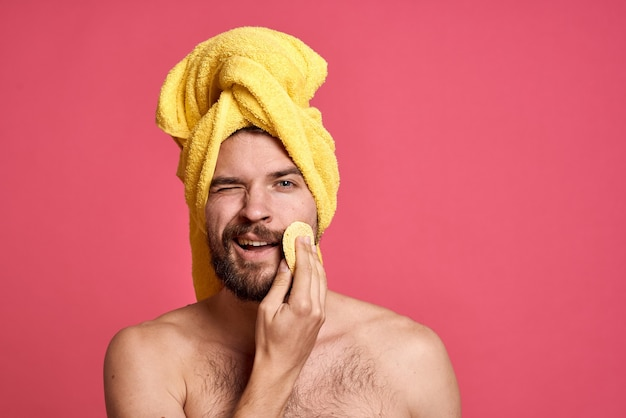 Homme aux épaules nues dans une serviette jaune sur sa tête éponge propre soins de la peau rose