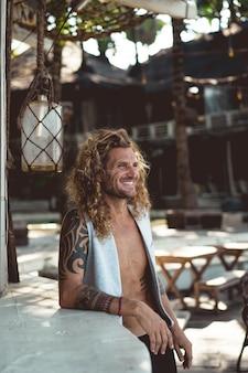Un homme aux longs cheveux bouclés dans un lieu de pêche. pêcheur sur l'océan