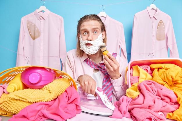 Homme aux longs cheveux roux occupé à repasser des vêtements et à se raser en même temps qu'il est pressé de travailler pendant son sommeil