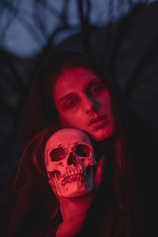 Homme aux lumières rouges tenant un crâne par la tête