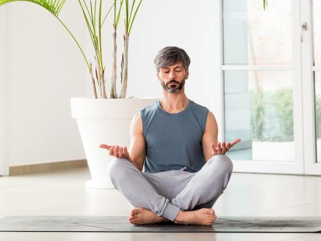 Homme aux pieds nus méditant dans la pose padmasana ou lotus avec une expression sereine sur le sol d'une pièce haute clé avec espace pour copie dans un concept de bien-être, de santé et de relaxation mentale