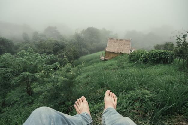 Homme aux pieds nus portant un jean accroché à la montagne dans le brouillard à la forêt tropicale le matin