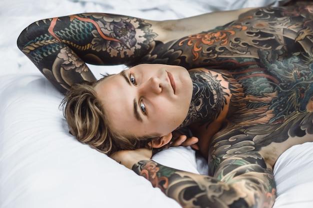 Homme aux tatouages colorés posant sur une feuille blanche