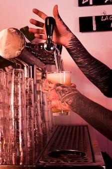 Homme aux tatouages produisant de la bière artisanale