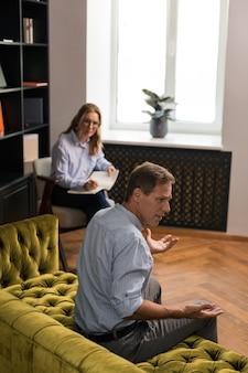Homme aux yeux bleus aux cheveux bruns indigné assis sur le canapé tout en parlant et en gesticulant