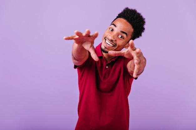 Homme aux yeux bruns avec un sourire heureux posant. modèle masculin africain spectaculaire en riant.