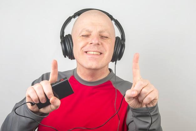 L'homme aux yeux fermés écoute de la musique avec des écouteurs