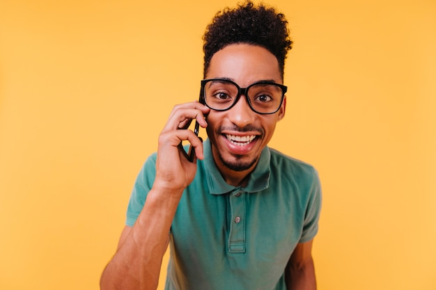 Homme aux yeux sombres intéressé à lunettes parler au téléphone. heureux mec africain porte des vêtements verts posant avec smartphone.