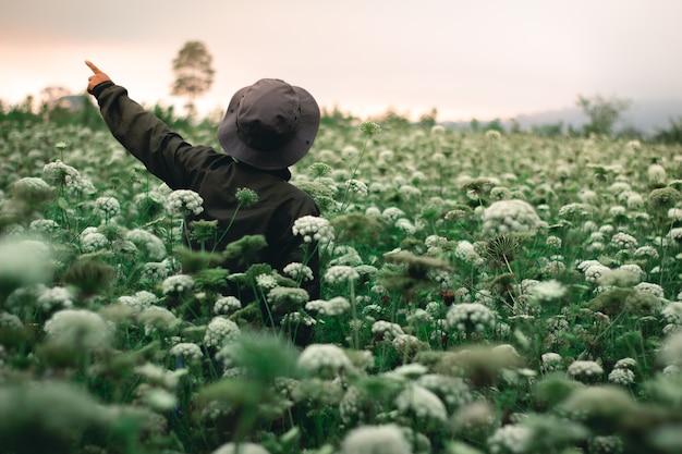 Homme d'aventure avec la fleur sauvage autour de lui