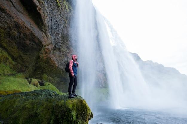 Homme d'aventure par la cascade de skogafoss, nature sur l'islande. parc national de vatnajökull. jeune homme visitant le paysage naturel.