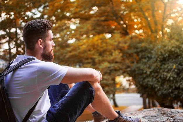 Homme aventureux avec sac à dos, assis sur un mur, profitant du paysage automnal.