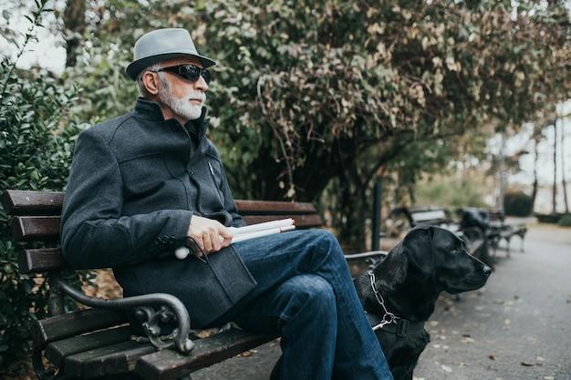 Homme aveugle mature avec une longue canne blanche assis dans un parc avec son chien-guide.