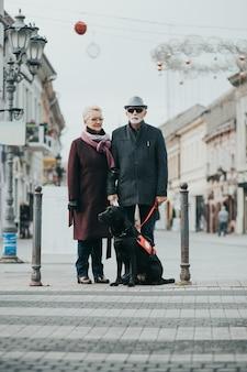 Homme aveugle mature avec une longue canne blanche et sa femme marchant avec leur chien-guide.
