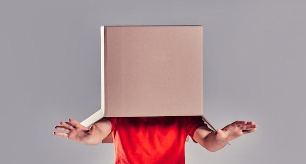 Homme aveuglé par la boîte à mettre sur sa tête sur fond gary.