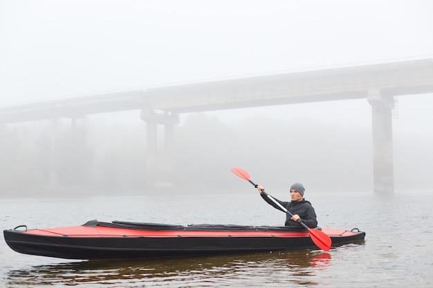 Homme aviron en bateau le matin brumeux, tenant la pagaie dans les mains, posant dans l'eau