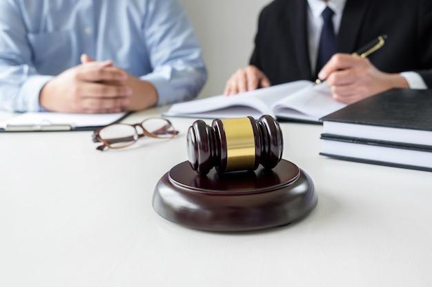 Homme avocat ou juge consulter un client et travailler avec des livres de droit