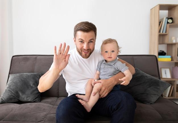 Homme ayant un appel vidéo avec sa famille tout en tenant son bébé