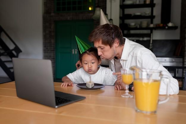 Homme ayant un appel vidéo avec sa femme le jour de l'anniversaire de leur fille