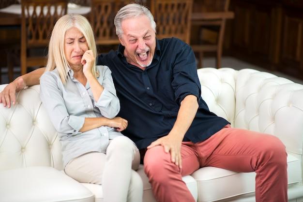 Homme ayant un bon rire pendant que sa femme pleure