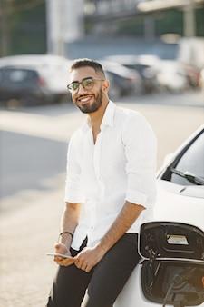 Homme ayant une conversation mobile en attendant une voiture électrique. borne de recharge, voitures écologiques. ethnie arabe.