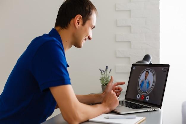 Homme ayant une conversation vidéo avec un médecin sur un ordinateur portable à la maison