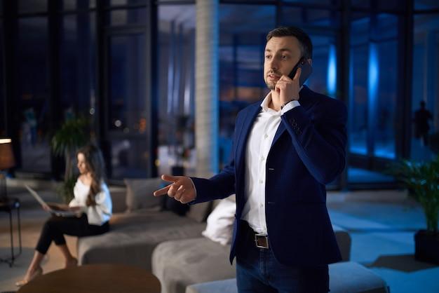 Homme ayant des conversations mobiles pendant que la femme travaille sur un ordinateur portable