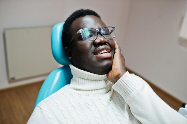 Homme ayant mal aux dents assis dans un fauteuil dentaire et besoin d'aide, patient de sexe masculin dans la douleur