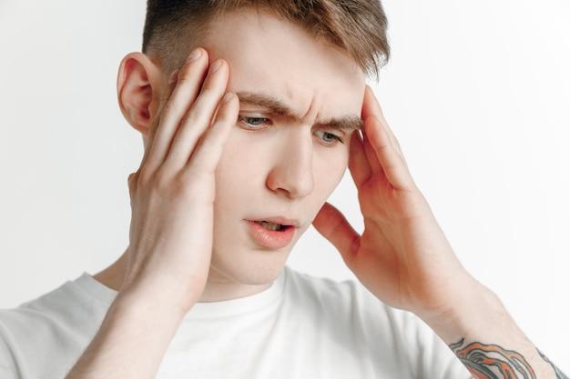Homme ayant mal à la tête. homme d'affaires debout avec douleur isolée sur studio gris