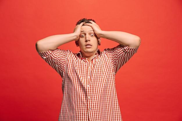 Homme ayant mal à la tête. isolé sur rouge. homme d'affaires debout avec douleur isolée sur rouge à la mode. portrait demi-longueur mâle