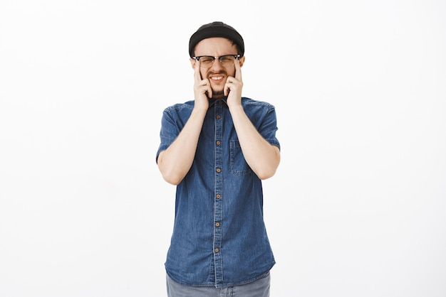 Homme ayant une mauvaise vue, toucher les yeux et plisser les yeux dans les lunettes grimaçant pendant le test de la vue en magasin d'opticien debout intense et concentré ayant besoin de porter des lunettes prescrites