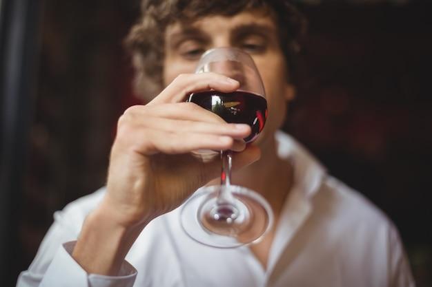 Homme ayant un verre de vin rouge