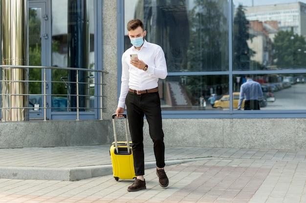 Homme avec des bagages portant un masque