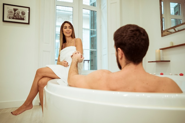 Homme, baignoire spa, tenant main, de, femme souriante