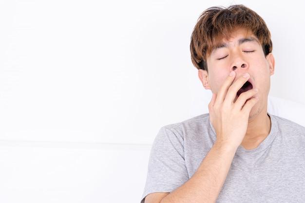 Homme bâillant et couvrant la bouche avec la main